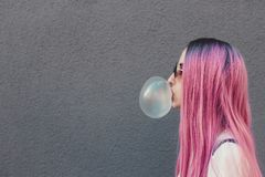 Stylish young hipster woman with long pink hair blowing a bubble with bubble gum. stock image