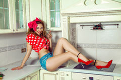 Stylish young lady with curly hair posing in the kitchen with gl Stock Images