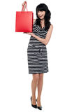 Stylish young lady presenting shopping bag Stock Images