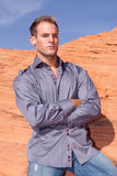 Stylish young man. On red rocks Stock Images