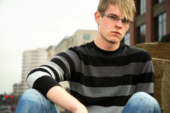 Stylish young man. A stylish young man with a striped pullover sweater and blue jeans Royalty Free Stock Photography