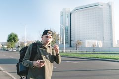 Stylish young man with a backpack strolling down the street and listening to music in headphones against the backdrop of the city. Royalty Free Stock Photos