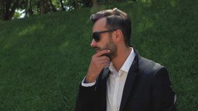Stylish young man with a beard in a classic suit puts on sunglasses, then straightens his beard and drinks tea or coffee from a. Disposable cup. businessman. 4k stock video footage