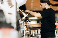 A stylish young man with beard,wearing casual clothes,cooks coffee in a coffee machine in a cozy coffee shop. royalty free stock photography
