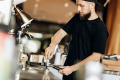 A stylish young man with beard,wearing casual clothes,cooks coffee in a coffee machine in a cozy coffee shop. royalty free stock image