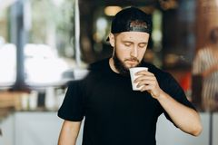 A stylish young man with beard,wearing casual outfit,stands and smells coffee in a modern coffee shop. royalty free stock photo