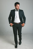 Stylish young man with black suit and bow. Royalty Free Stock Images
