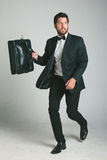 Stylish young man with black suit and briefcase. Stock Photos
