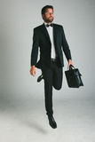 Stylish young man with black suit and briefcase. Royalty Free Stock Photo