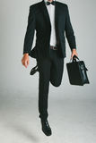 Stylish young man with black suit and briefcase. Royalty Free Stock Photos