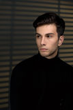 Stylish young man in a black sweater sits near blinds and thinki Royalty Free Stock Photo