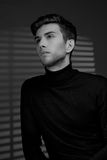 Stylish young man in a black sweater sits near blinds and thinki Royalty Free Stock Photography
