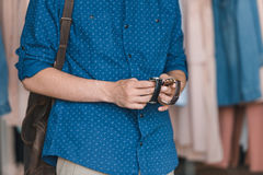 Stylish young man choosing wristwatches in boutique. Cropped shot of stylish young man choosing wristwatches in boutique Stock Image