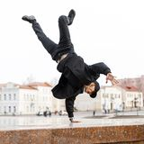 Stylish young man dancer in black jeans in a stylish jacket in a cap in sunglasses does a handstand in the city on the street. American hipster guy royalty free stock photography