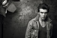 Stylish young man in a denim jacket. Conceptual black and white fashion portrait. Look and men`s hairstyle Royalty Free Stock Photo