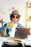 Stylish Young Man Drinking Orange Juice While Working on Summer. Vacation Season at Office Stock Images