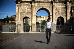 Stylish young man in front of Arco di Costantino, Rome, Italy Royalty Free Stock Photography