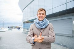 Stylish man in a gray coat with scraft on the street stock photo