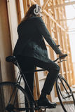 Stylish young man in headphones riding bicycle and looking away Royalty Free Stock Photography
