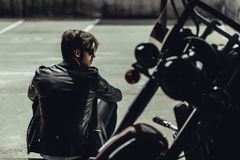 Stylish young man in leather jacket sitting near motorbike and looking away Royalty Free Stock Photos