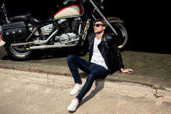 Stylish young man in leather jacket and sunglasses sitting on concrete curb near motorbike Stock Photography