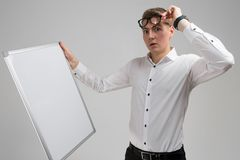 Portrait of surprised young man wearing glasses with clean magnetic Board isolated on white background. Stylish Young man lifted his glasses and looks at white royalty free stock photo