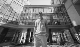 Stylish young man posing against modern glass building Stock Photography