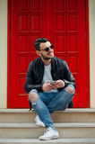 Stylish young man posing on background of red door in sunny street. Stock Photos
