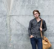 Stylish young man posing with travel bag Royalty Free Stock Images