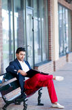 Stylish young man resting on a bench. Royalty Free Stock Photography