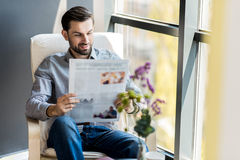 Stylish young man resting with paper. Good news. Portrait of cheerful pleasant bearded guy is reading newspaper while sitting against window with smile Royalty Free Stock Photography