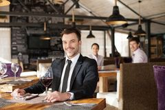 Stylish young man sitting in restaurant. Stock Photography