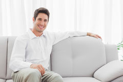 Stylish young man sitting on sofa. Smiling at camera Royalty Free Stock Images