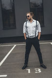 Stylish young man smoking cigarette and standing with hands in pockets. Handsome stylish young man smoking cigarette and standing with hands in pockets Royalty Free Stock Photography