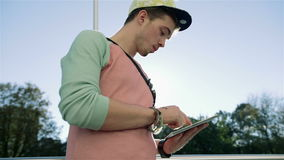 Stylish young man in the street using tablet in the city. stock video