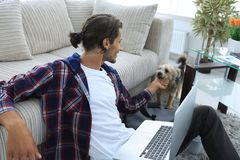 Stylish young man stroking his pet and working on laptop Royalty Free Stock Images