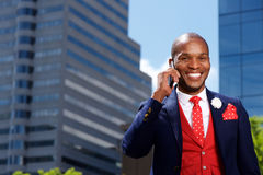 Stylish young man in suit using mobile phone outdoors in city Royalty Free Stock Image