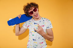 Stylish young man in sunglasses holding skateboard. And looking at camera isolated over yellow background Stock Photography