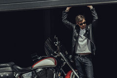 Stylish young man in sunglasses and leather jacket standing in garage with motorbike. Handsome stylish young man in sunglasses and leather jacket standing in Royalty Free Stock Photos
