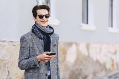 Stylish young man in sunglasses with phone on street royalty free stock photography