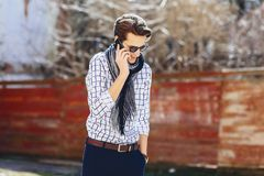 Stylish young man in sunglasses with phone on street. Stylish young man in sunglasses with phone walk on street Royalty Free Stock Photography