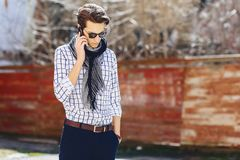 Stylish young man in sunglasses with phone on street. Stylish young man in sunglasses with phone walk on street Stock Images