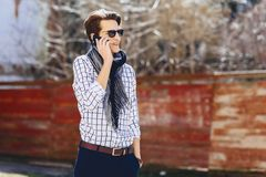 Stylish young man in sunglasses with phone on street. Stylish young man in sunglasses with phone walk on street Royalty Free Stock Photo