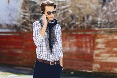 Stylish young man in sunglasses with phone on street. Stylish young man in sunglasses with phone walk on street Stock Image