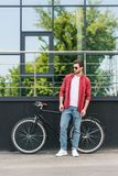 Stylish young man in sunglasses standing near bicycle at city. Street royalty free stock images