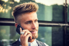 Stylish young man talking on phone outdoor standing Royalty Free Stock Photos