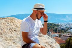 Stylish man un sunglasses looks at the city view from the high hill stock photos