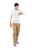 Stylish young man walking and checking time on wrist watch Royalty Free Stock Images