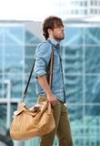 Stylish young man walking with travel bag Stock Images