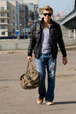 Stylish young man walks with big travel bag Royalty Free Stock Image